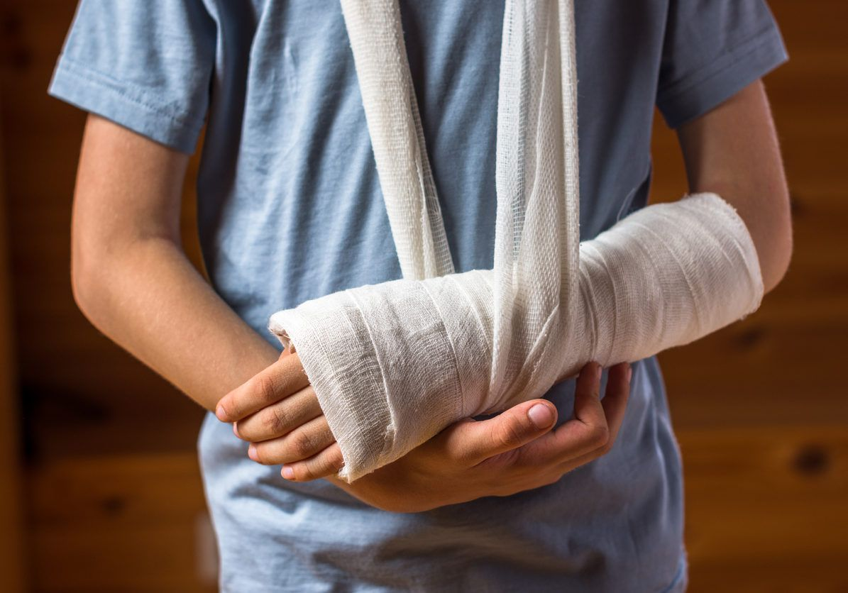 Boy with an arm in plaster indoors on the brown background , careless behavior at home, being in hospital, injury and health concept